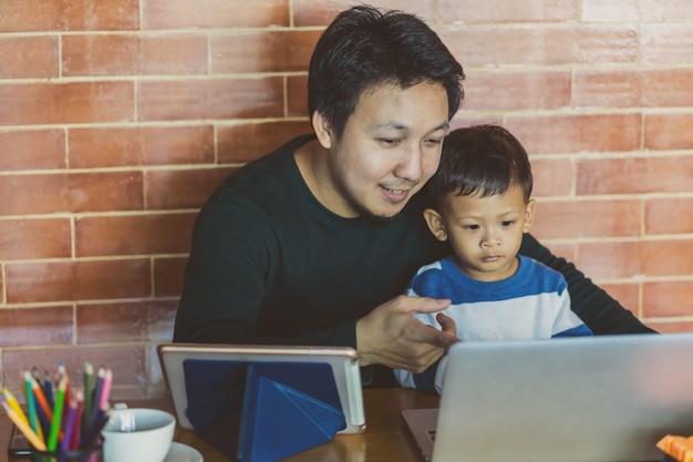 Pai solteira asiática com filho está olhando os desenhos animados via laptop de tecnologia juntos Foto Premium
