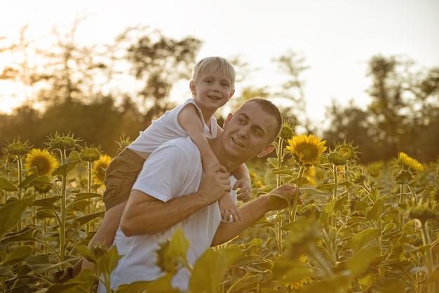 Pai sorridente feliz com o filho nas costas, andando em um campo verde de girassóis florescendo Foto Premium