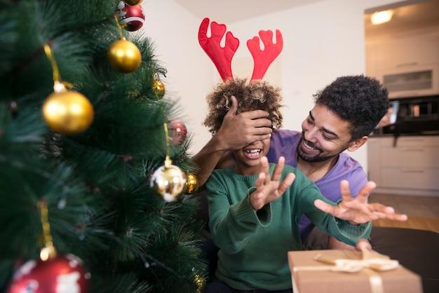 Pai surpreendendo a filha com presente perto da árvore de natal Foto gratuita