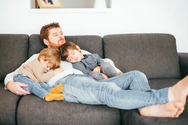 Pai tirando soneca com filhos no sofá Foto gratuita