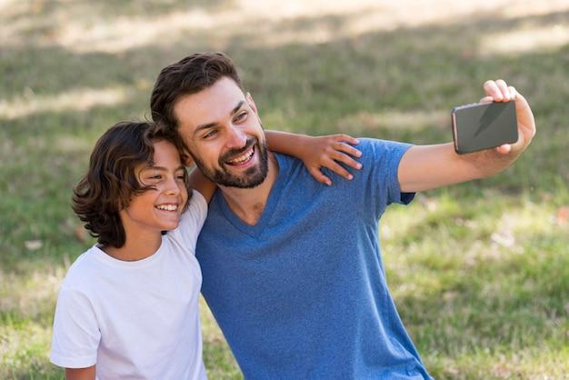 Pai tirando uma selfie com o filho ao ar livre Foto gratuita