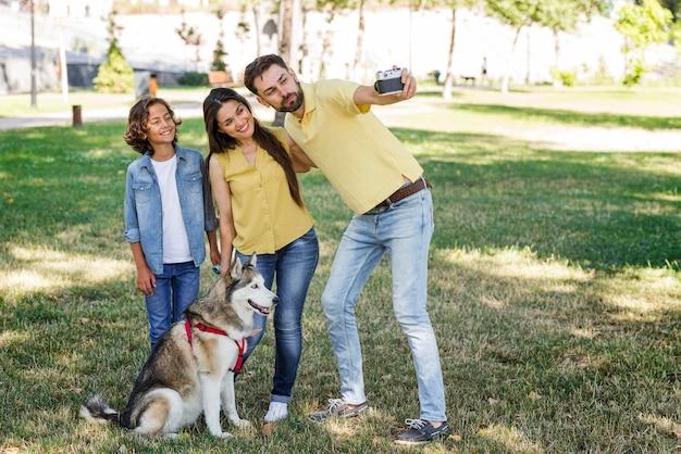 Pai tirando uma selfie da esposa e filho no parque com o cachorro Foto gratuita