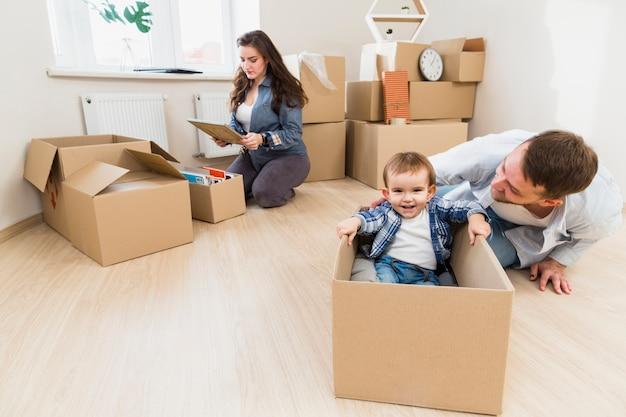 Pai, tocando, com, seu, filho, e, seu, esposa, desembalando, caixa papelão, em, fundo Foto gratuita