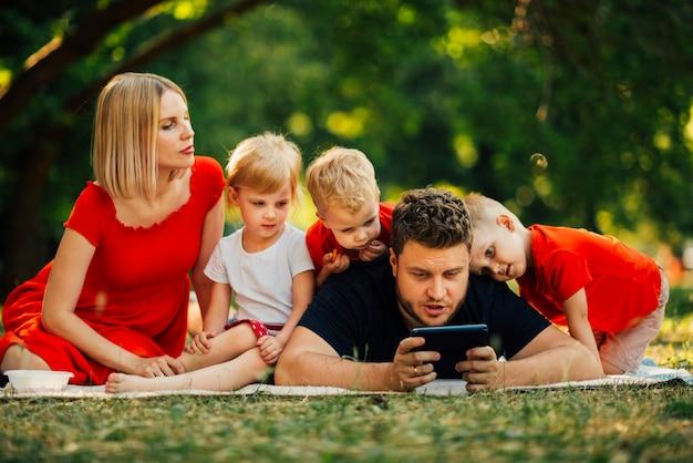 Pai, tocando, telefone, e, crianças, observar Foto gratuita