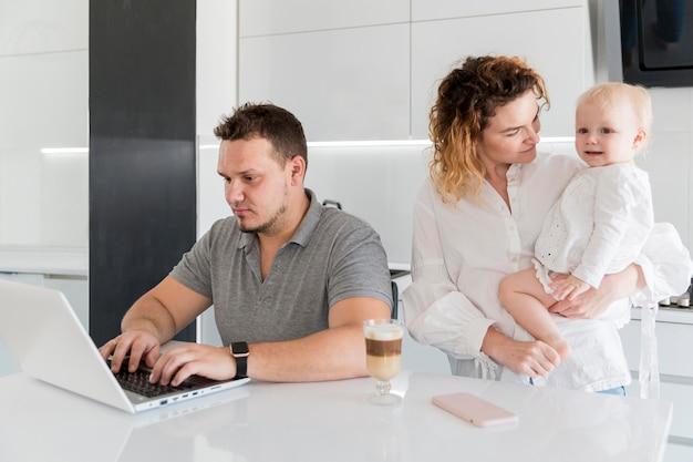 Pai trabalhando no laptop Foto gratuita