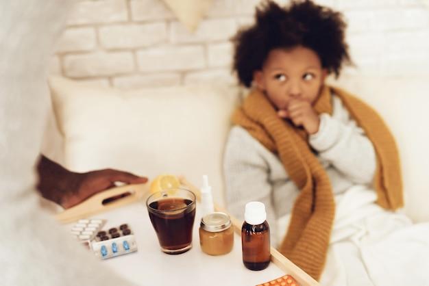 Pai traz filha tosse medicina e chá. Foto Premium
