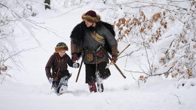 Pai viking com seu filho indo na floresta de inverno, eles tendo machado, lança, cebola. Foto Premium