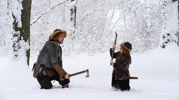 Pai viking com seu filho na floresta de inverno. Foto Premium