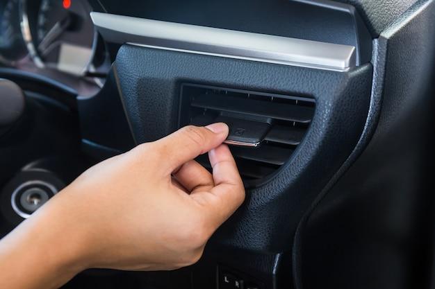 Painel da grade do sistema de condicionamento de ar do carro do controle da mão no console Foto Premium