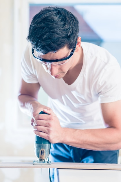Painel de madeira de corte diy trabalhador com serra Foto Premium