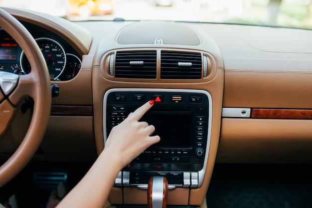 Painel do carro. close up do rádio. mulher liga o rádio Foto gratuita