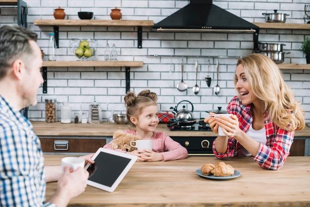 Pais alegres e filha desfrutando de pequeno-almoço na cozinha Foto gratuita