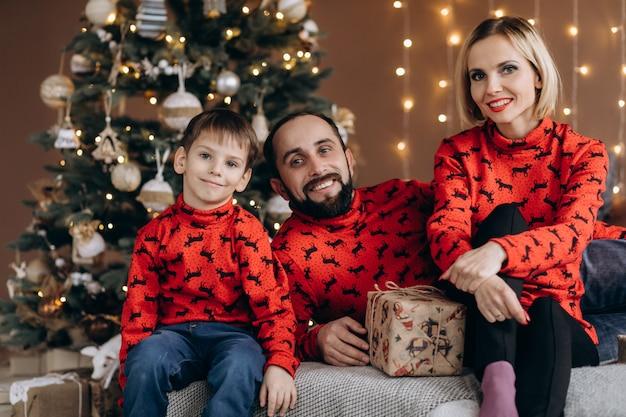 Pais atraentes e seu filho pequeno em blusas vermelhas se divertem abrindo presentes antes de um natal Foto gratuita