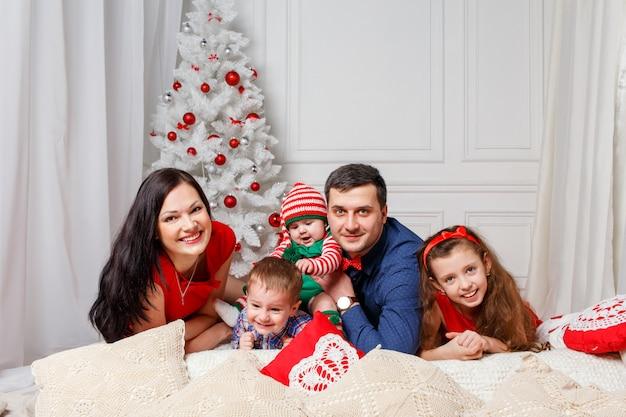 Pais com filhos em uma sessão de fotos de natal Foto Premium