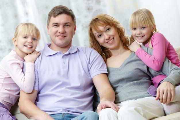 Pais com suas filhas que sentam-se no sofá Foto gratuita