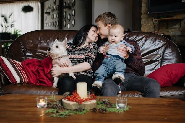 Pais com um bebê no natal e um cão sentado no sofá Foto gratuita