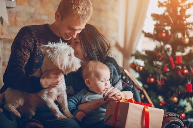 Pais com um cão e um bebê com um fundo da árvore de natal Foto gratuita