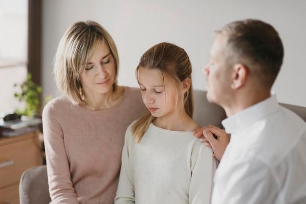 Pais e filha orando juntos Foto gratuita