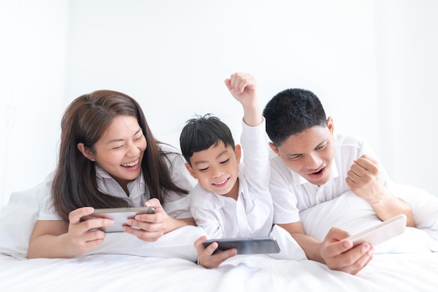 Pais e filho jogando videogame smartphone em casa Foto Premium