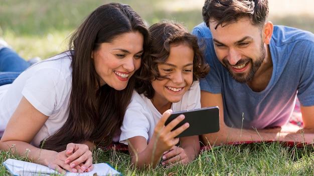 Pais e filhos assistindo a algo no smartphone enquanto estão no parque Foto gratuita