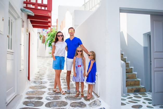 Pais e filhos na rua da aldeia tradicional grega típica na ilha de mykonos, na grécia Foto Premium