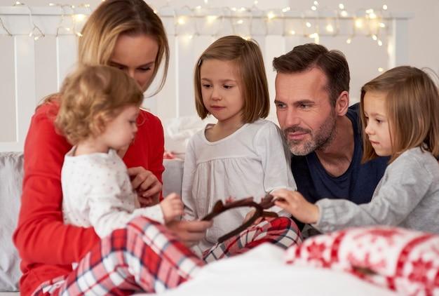 Pais e filhos passando a manhã de natal na cama Foto gratuita