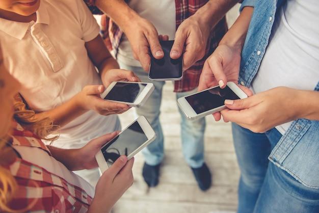 Pais e seus filhos usando smartphones. Foto Premium