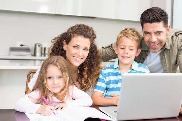Pais felizes colorindo e usando laptop com seus filhos Foto Premium
