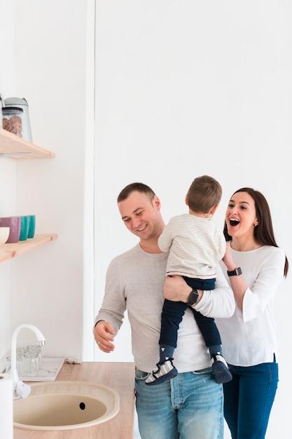 Pais felizes com criança na cozinha Foto gratuita
