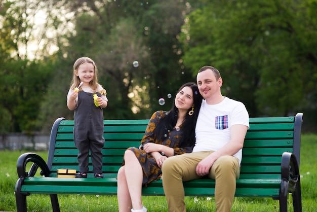 Pais felizes com criança na natureza Foto gratuita