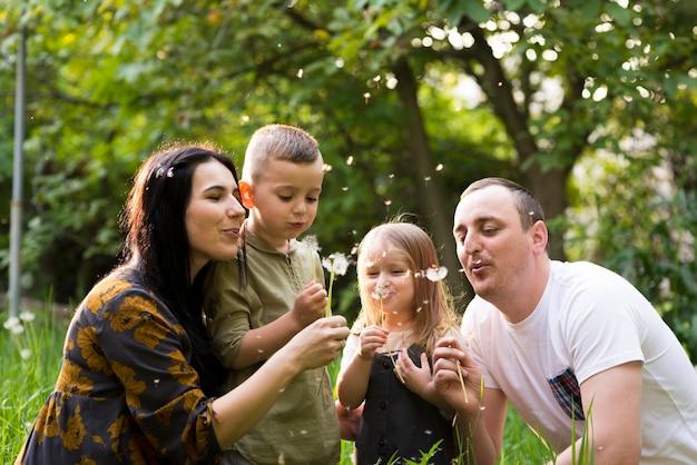 Pais felizes com crianças na natureza Foto gratuita