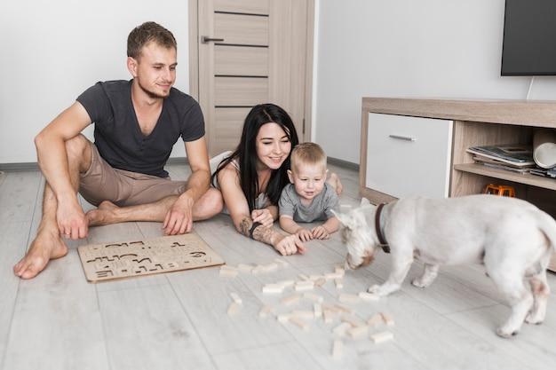 Pais felizes com seu filho pequeno olhando cão cheirando blocos de madeira Foto gratuita