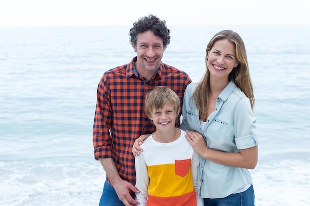 Pais felizes em pé com o filho pelo mar Foto Premium