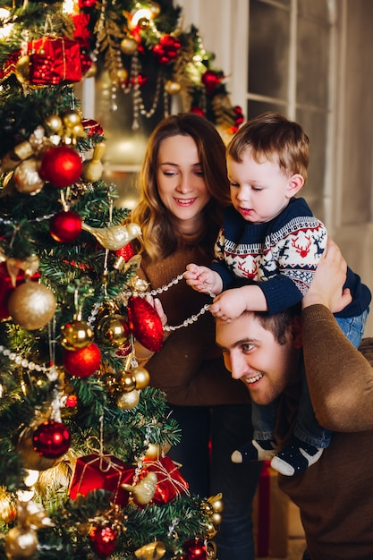 Pais felizes, mostrando a decoração de natal na árvore para o filho pequeno. Foto Premium