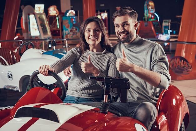 Pais felizes no parque de diversões sentado no carro de brinquedo Foto Premium