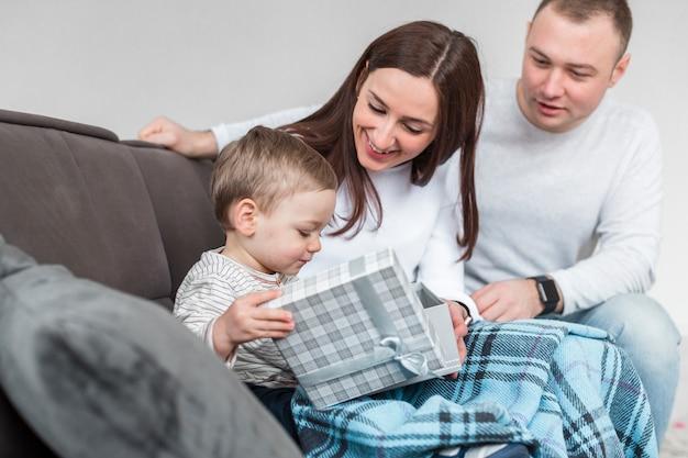 Pais felizes no sofá com bebê Foto gratuita