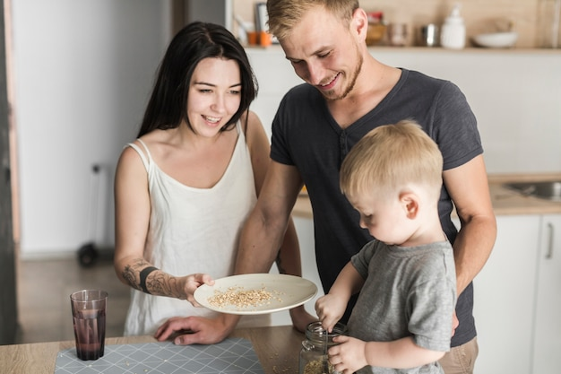Pais felizes olhando menino removendo a aveia da jarra no prato Foto gratuita