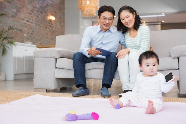 Pais felizes, olhando para a filha do bebê na sala de estar Foto Premium