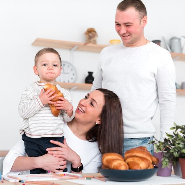 Pais felizes, segurando a criança com croissant Foto gratuita