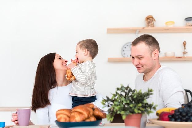 Pais felizes, segurando a criança na cozinha Foto gratuita