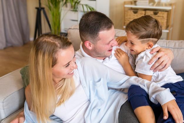Pais felizes, segurando seu filho e sentado na sala de estar Foto gratuita