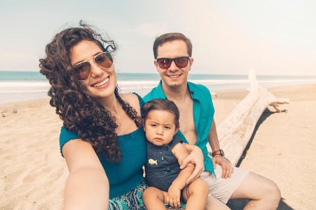 Pais felizes, sorrindo e tomando selfie na praia. Foto gratuita