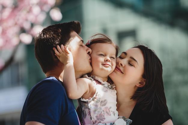 Pais jovens felizes com uma pequena filha ficar debaixo de floração rosa fora Foto gratuita