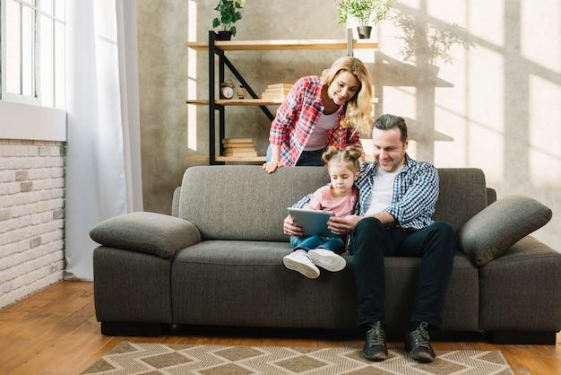 Pais, relaxante, com, seu, criança, usando, tablete digital, em, lar Foto gratuita