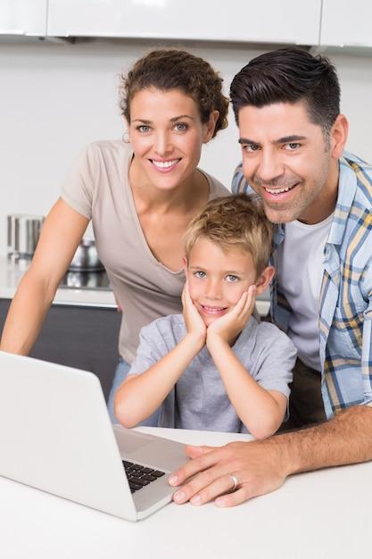 Pais sorridentes usando laptop com seu filho Foto Premium