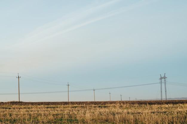 Paisagem atmosférica com linhas elétricas no campo amarelo sob o céu azul. Foto Premium