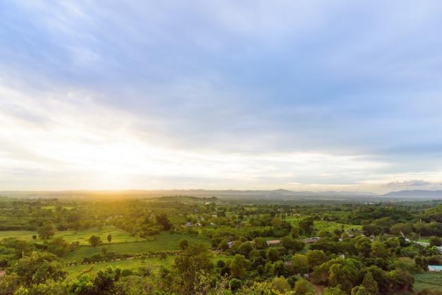 Paisagem azul e verde do nebuloso, da montanha e da floresta com por do sol na noite da vista superior. Foto Premium