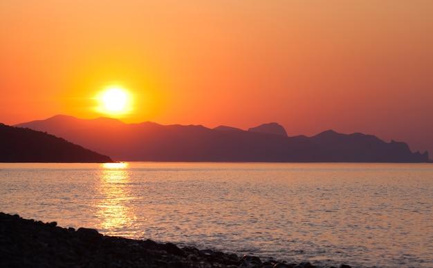 Paisagem cênica de sol do mar calmo contra o pano de fundo de altas colinas ou montanhas durante as férias de verão Foto Premium