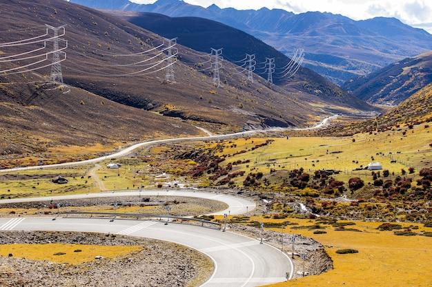 Paisagem colorida com uma bela estrada de montanha com um asfalto perfeito altas pedras no céu azul ao nascer do sol no verão Foto Premium