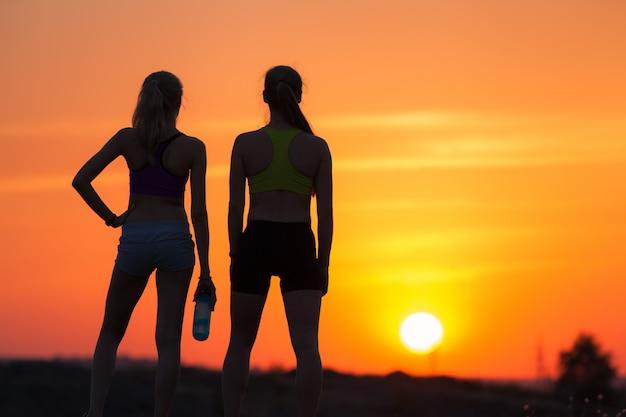 Paisagem com silhueta de jovens desportivos ao pôr do sol Foto Premium